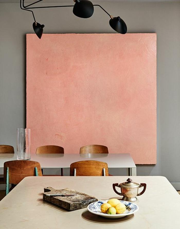 peinture décorative rose saumon, lampe noire, chaises en bois, table blanche longue