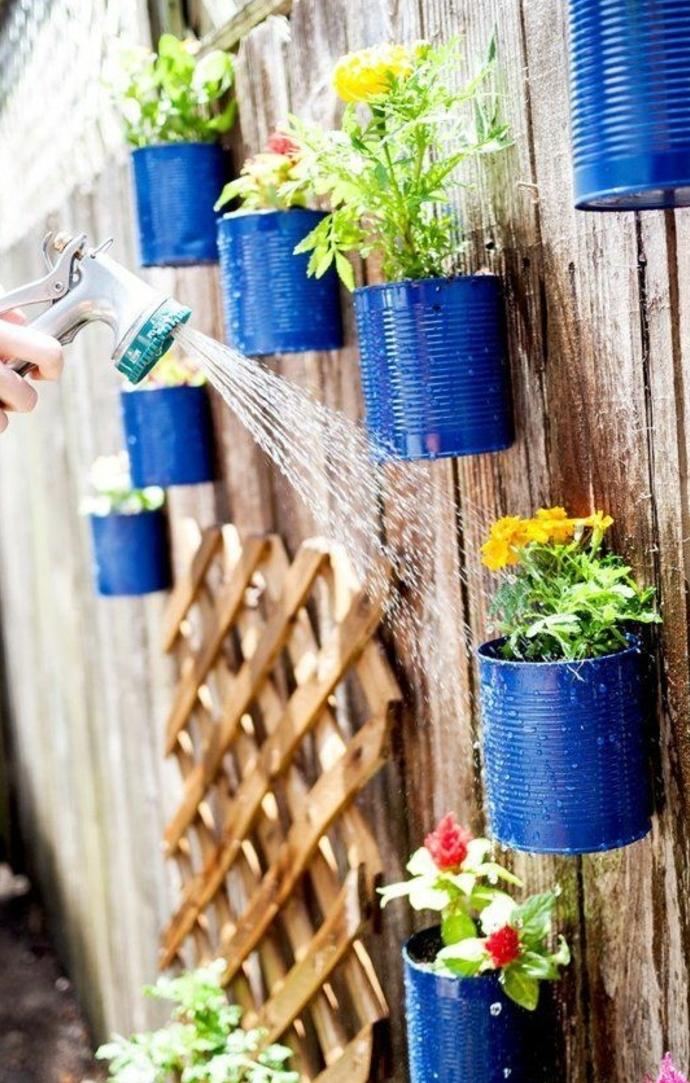 idée de jardinière sur une palissade en bois, deco boite conserve exterieure, grosse boite de conserve repeinte en bleu, diy pot de fleur, fleurs multicolores