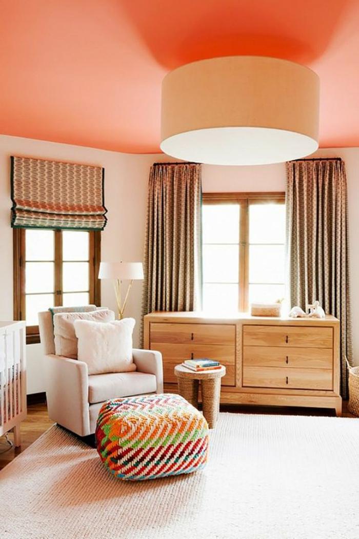 plafond couleur dofus, grand plafonnier, fauteuil blanc, commode en bois