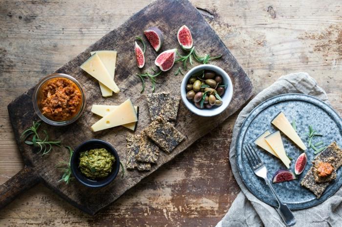 un plateau de fromages accompagné de pesto et de la tapenade, plateau antipasti aux sauces maison