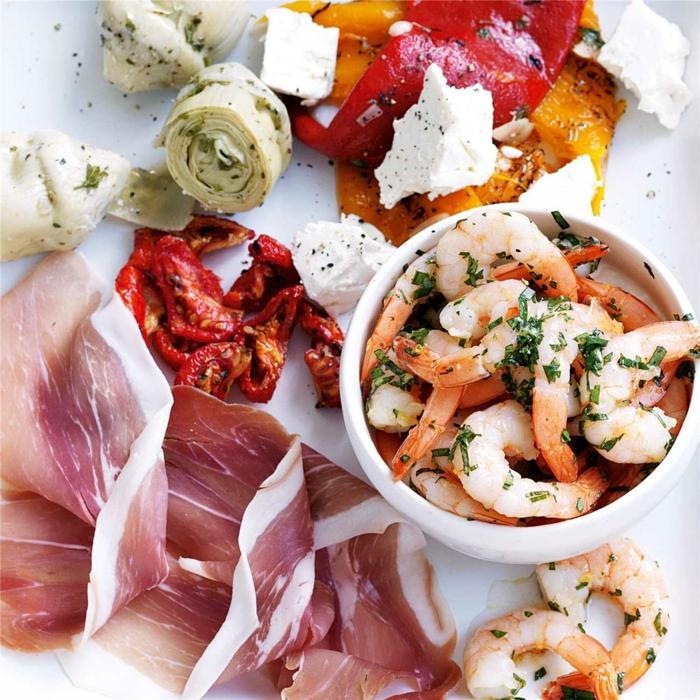 délicieux plateau antipasti composé de crevettes marinées, des tranches de prosciutto, des tomates séchées et des coeurs d'artichauts