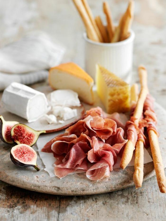 des gressins enrobés de prosciutto sur un plateau de charcuterie et fromages