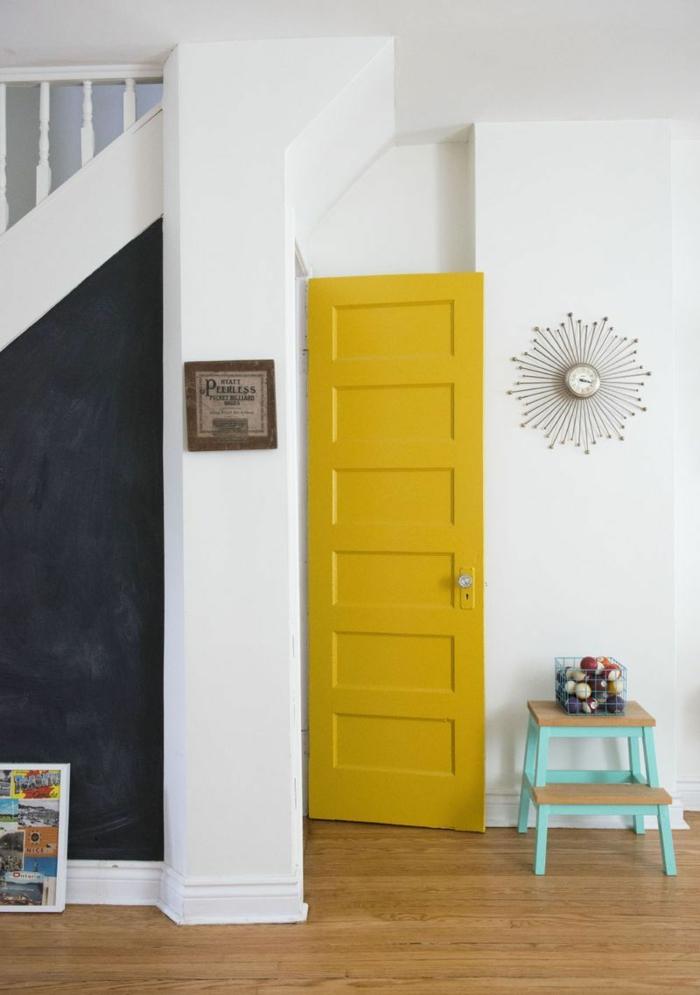 une porte en ocre jaune vive en contraste avec le pan de mur en ardoise