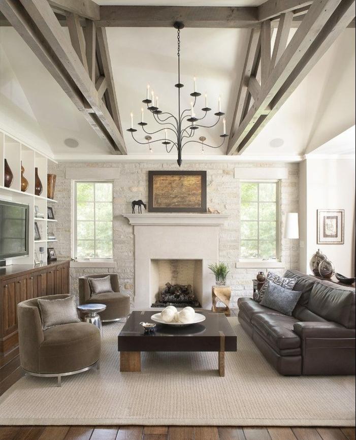 canapé en cuir, tapis gris clair, table design, fauteuil gris, parquet en bois, poutre apparente, cheminée, mur d accent en pierre, étagères avec decoration, suspension design