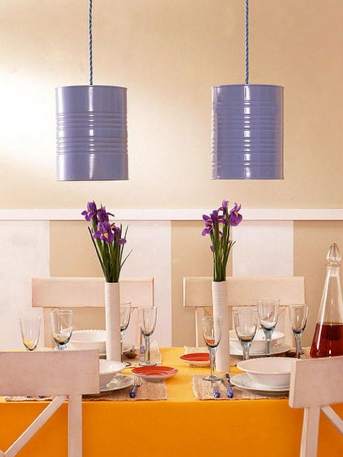 des abats jours en boite de conserve, repeinte en lilas au dessus d une table, nappe orange, chaises blanches, vaisselle, couverts, deco florale