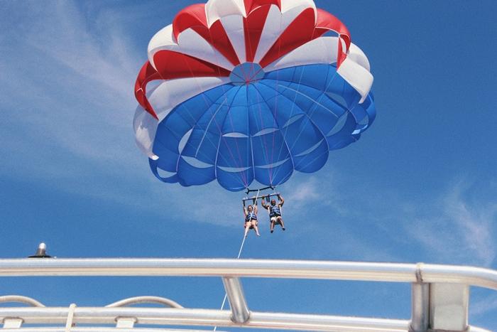 truc cool a faire quand on s ennuie, adrénaline, aventure, paravoile, couple, ciel bleu, parachute rouge et bleu