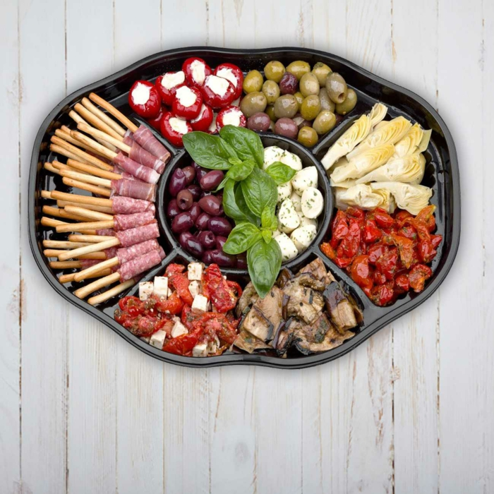une recette antipasti italien facile à préparer, plateau de prosciutto, d'artichauts marinés, de tomates séchées et de feta