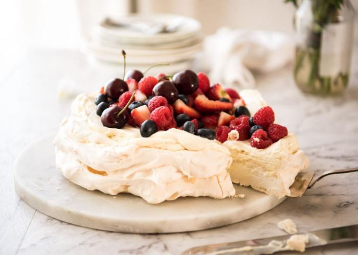 délicieuse pavlova aux fruits rouges, recette traditionnelle à base de meringue et au glaçage mousseux de crème fouettée