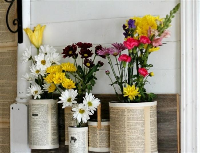 idée de recyclage boite de conserve, une jardinière constituée de boites de conserve attachées sur une planche en bois et customisées de papier journal, des cache pots originaux