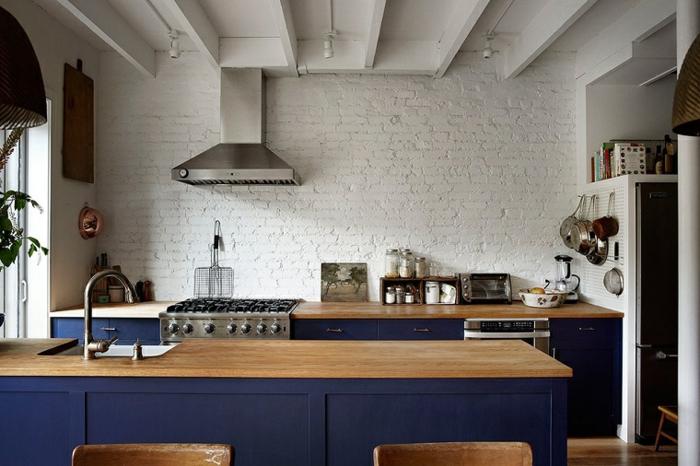 cuisine blanche et bois, îlot centrale en bois, murs en briques blanc, plafond avec poutres en bois, cuisine actuelle
