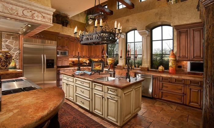 cuisine actuelle, îlot centrale en bois avec comptoir marron, bougeoir en fer forgé, carrelage sol foncé, cuisine équipée