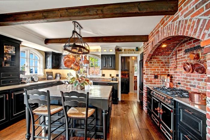 cuisine aménagée, chaises de bar en noir, fenêtre blanche, cuisine en bois, mur en brique, poêles en cuivre, cuisine intégrée