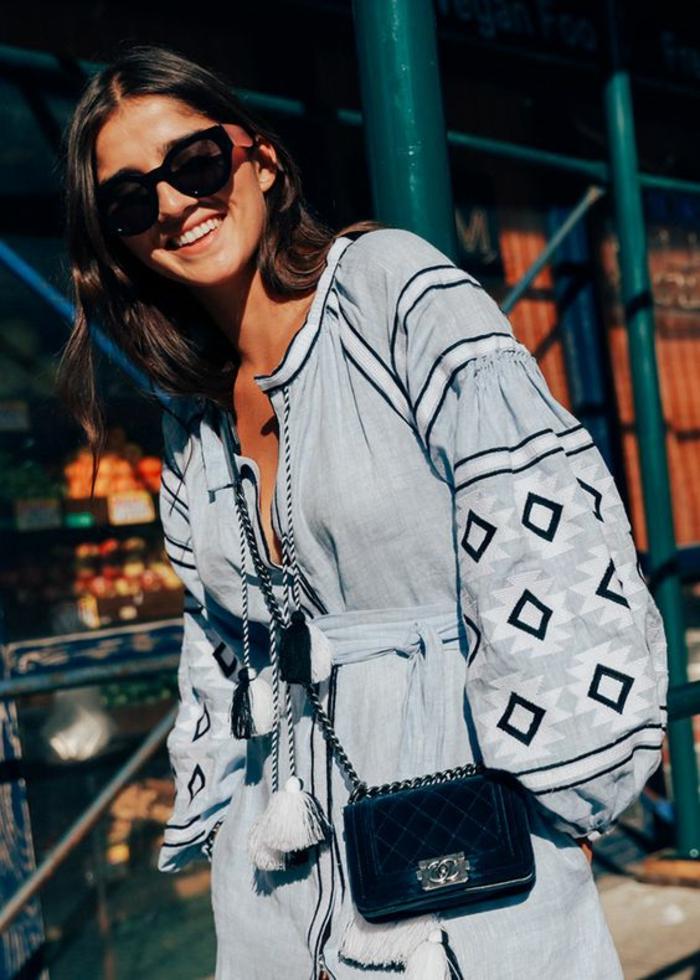 une maxi-robe fluide boutonnée devant avec lacets pompons combinée avec un sac bandoulière chic et des lunettes glamour