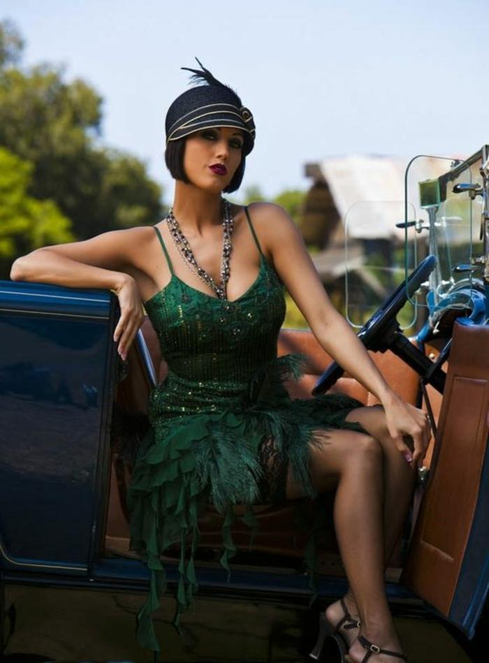 femme en robe charleston verte avec bretelles, chapeau cloche avec plume, cabriolet