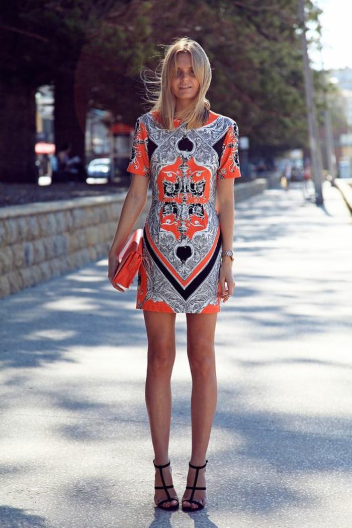 une mini-robe à l'imprimé ethnique portée avec des sandales à haut talon et sac pochette orange