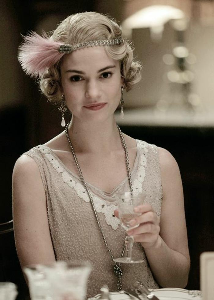 robe des années 20, couleur écru, serre-tête avec plume rose, boucles d'oreilles avec pendentifs blancs