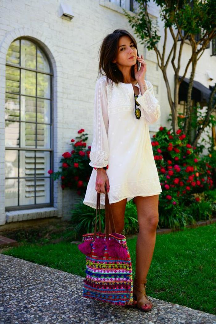une robe tunique blanche à manches bouffantes associée à un sac à main ethnique, look bohème chic en blanc