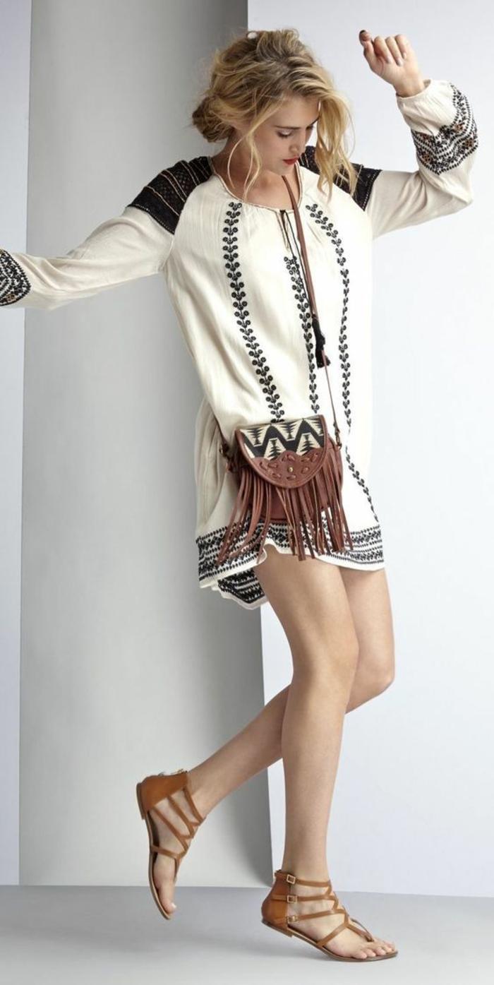 une robe tunique en noir et blanc à manche longue, look ethnique complété par des sandales plates spartiates et petit sac à main bandoulière avec franges