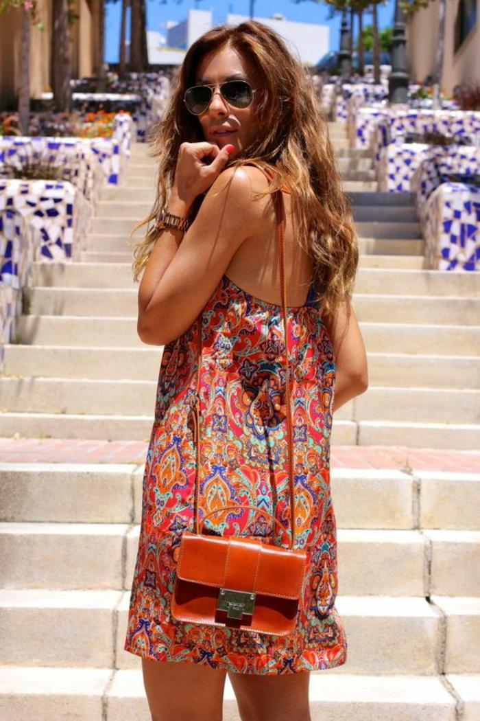une robe tunique aztèque sans manches associée avec un petit sac bandoulière en cuir vintage