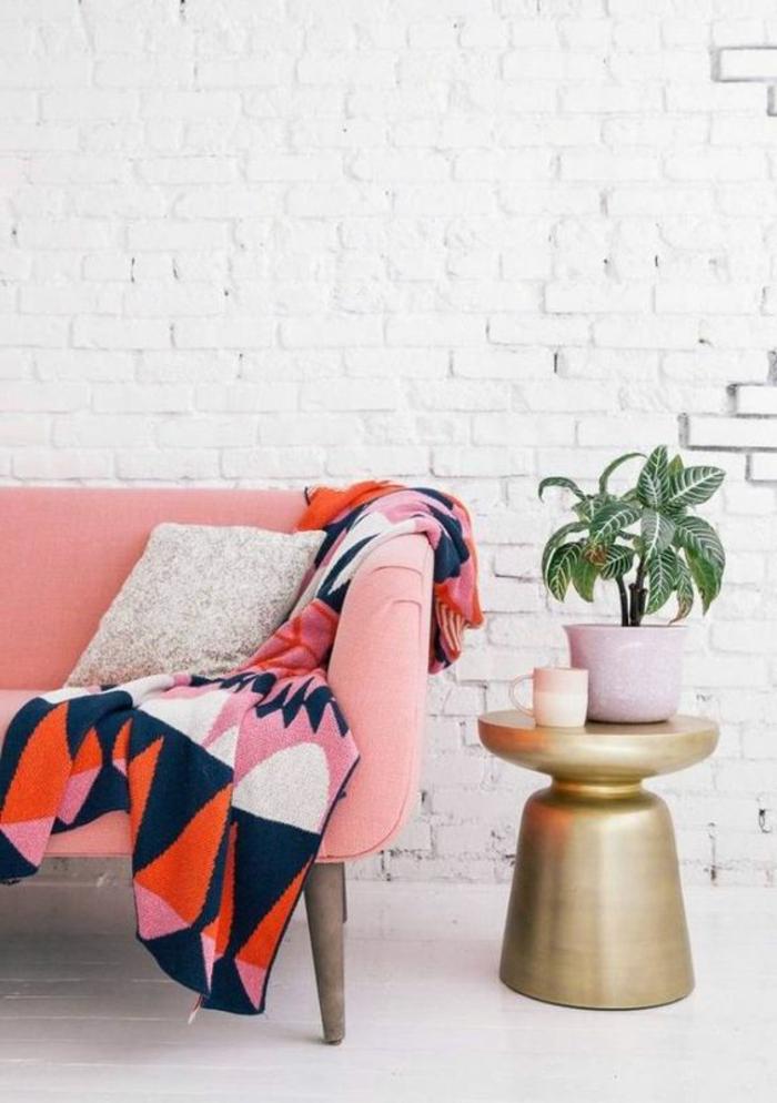 sofa rose corail et plaid de lit en couleurs radiantes, mur en briques blanches