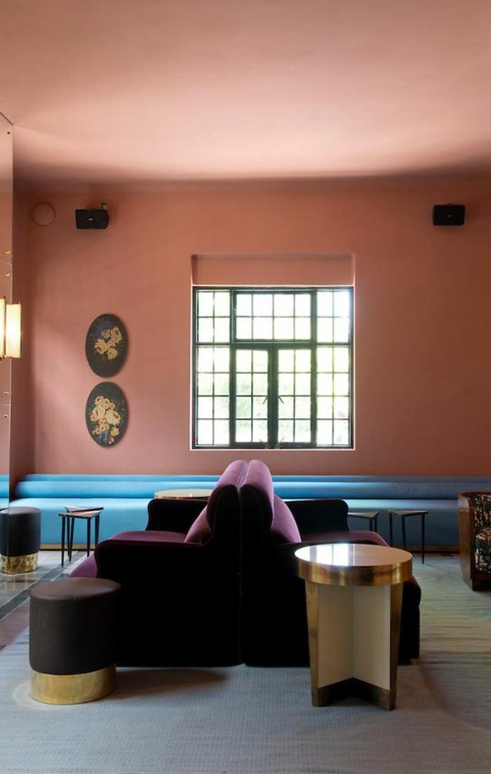 mur rose corail, sofas lilas, grand sofa bleu, fenêtre, intérieur simple et élégant