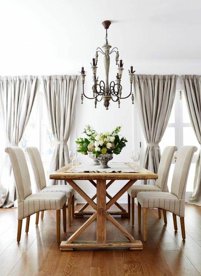 idée comment décorer une salle à manger, parquet clair, table campagne chic, chaises blanches, lustre baroque, rideaux gris, centre de table floral