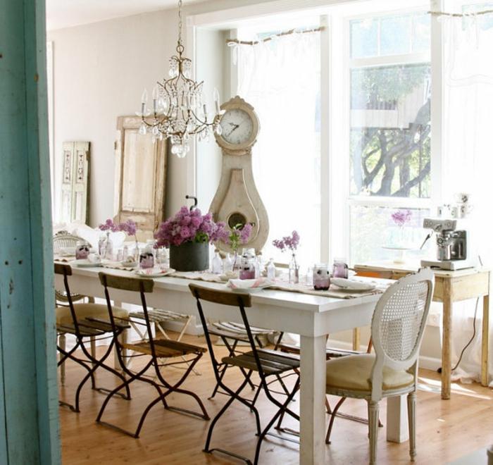 idée salle à manger campagne chic, table en bois blanche, chaise en bois et métal, horloge, lustre élégant, parquet clair, centre de table floral