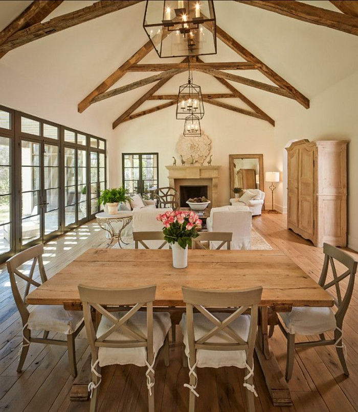 deco campagne chic, table et chaises salle à manger en bois, poutres apparentes, fauteuils blancs, parquet bois, suspensions lanternes, cheminée en pierre