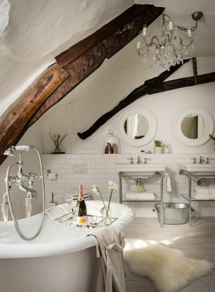 deco campagne chic salle de bain, baignoire à poser, poutres apparentes, carrelage blanc, miroirs ronds, lavabo console, tapis de fourrure