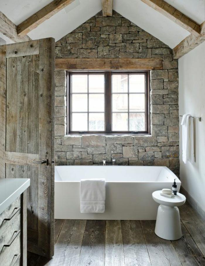 deco campagne salle de bain, mur en pierre, parquet et porte bois brut, baignoire à poser, poutres apparentes, serviette blanches