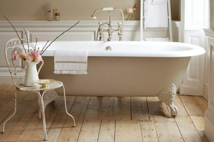 aménager une salle de bain campagne chic, baignoire à poser et peinture murale beige, chaise en métal, bouquet de fleurs