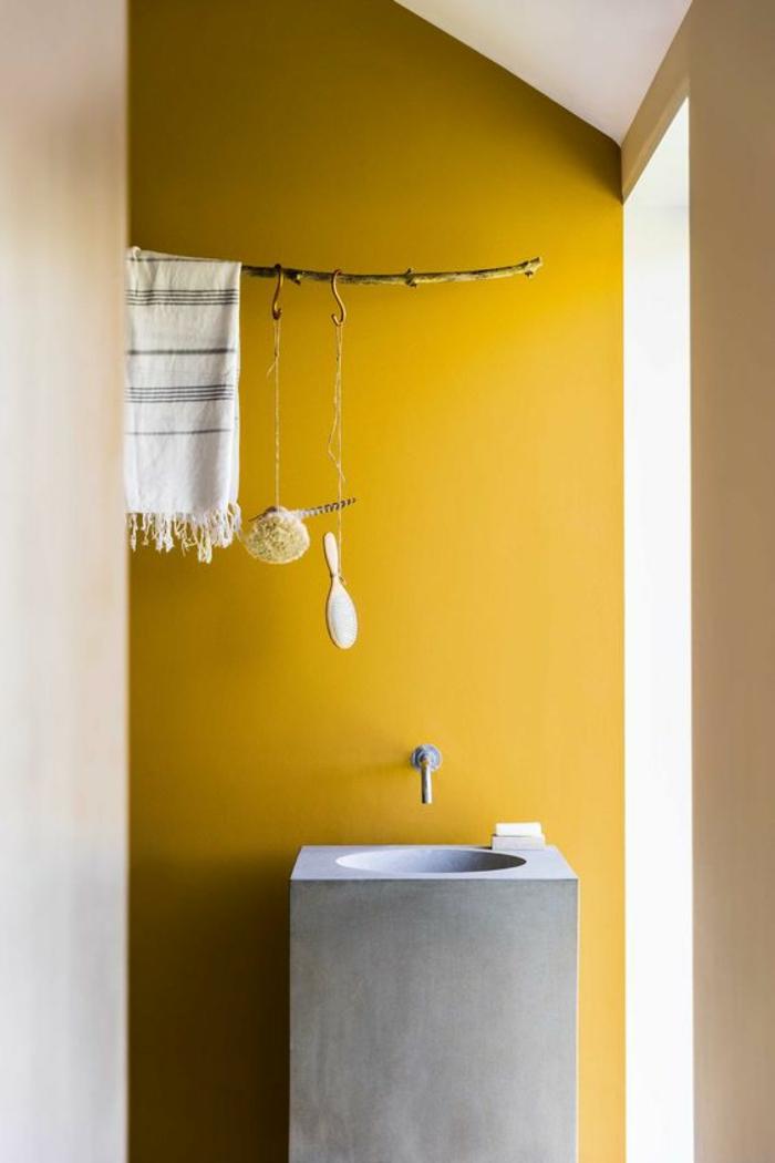 une salle de bains rustique aménagée sous pente illuminée par une peinture ocre