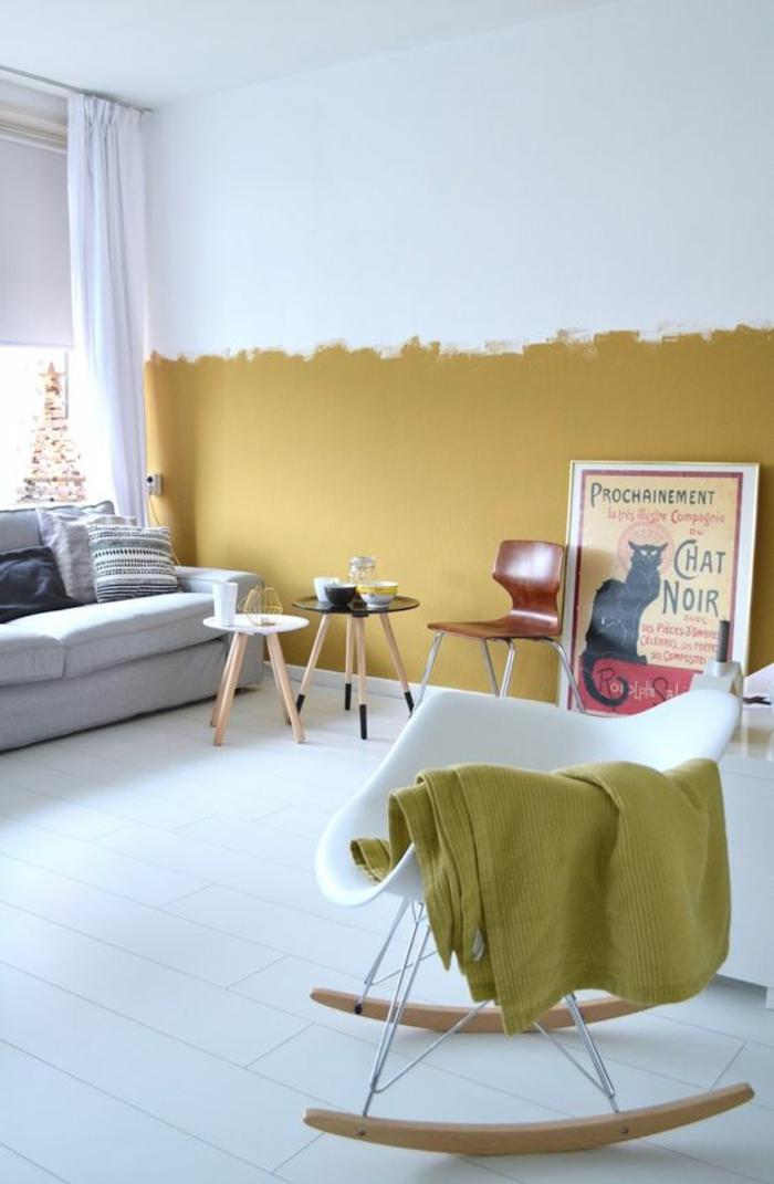 un salon au design scandinave et au plancher blanc dynamisé par la peinture ocre sur la moitié du mur