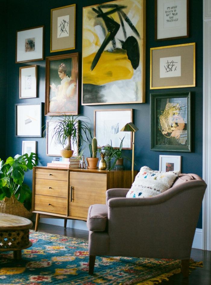 un salon bohème chic au mur bleu canard décoré de cadres, des nuances de l'ocre jaune sur le mur