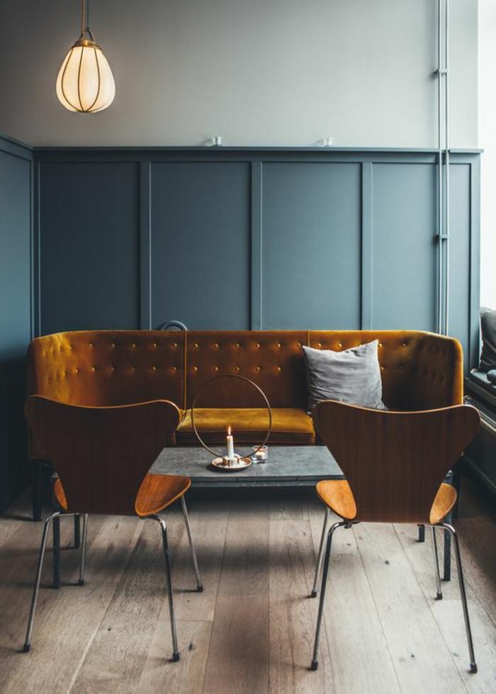 canapé ocre jaune en velours comme accent de luxe dans le salon vintage bleu canard