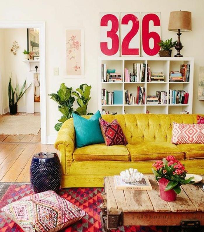idée comment aménager un salon bohème, canapé jaune, coussin bleu, deco bleu et jaune, bibliothèque, chiffre décoratifs mur, tapis oriental, table basse industrielle en bois