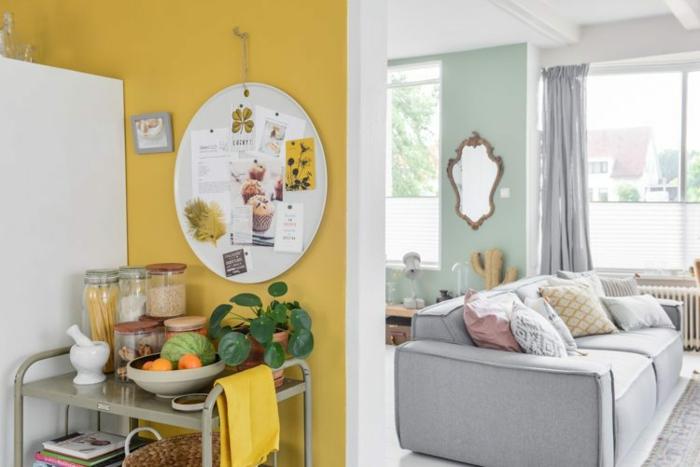 une cuisine ocre jaune ouverte sur un salon aux tons pastel
