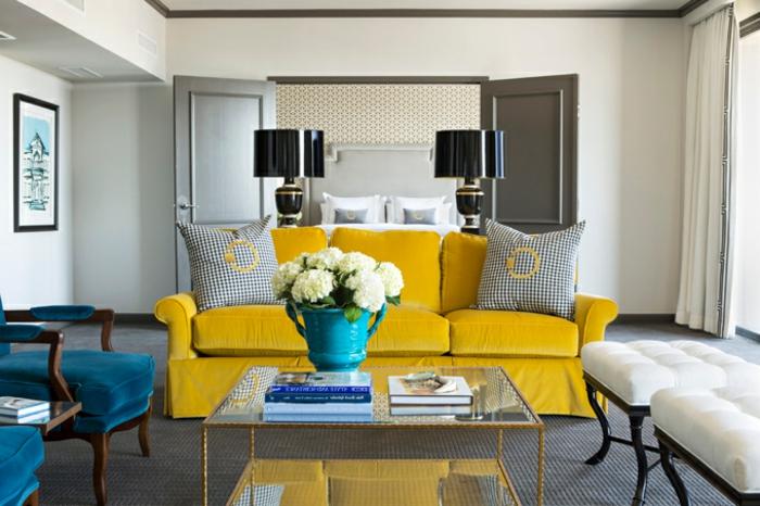 deco bleu et jaune dans un salon contemporain, chaises bleu canard, canapé jaune, table basse, tapis gris, tabourets en bois coussins blancs, lampes noirs stylées