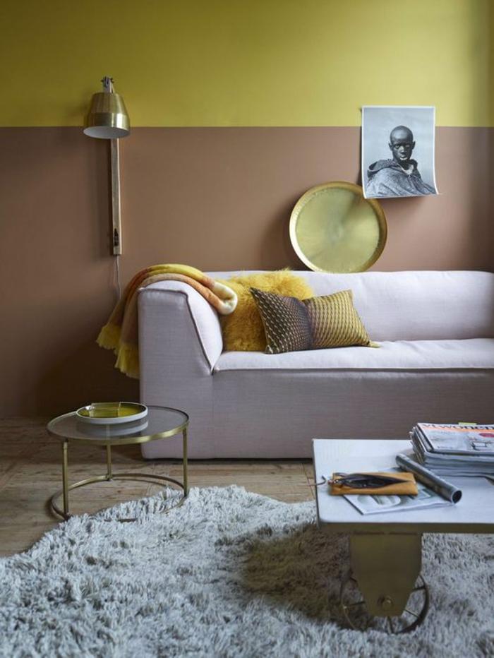 salon d'une ambiance chaleureuse et apaisante, mur bicolore de couleur ocre et d'or aux accent cuivré, canapé moderne rose pastel
