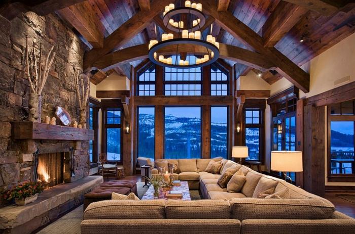 salon rustique avec cheminée en pierre, canapé d angle beige, tabourets marron, lustre avec bougies, grandes fenêtres, vue montagne, poutre apparente