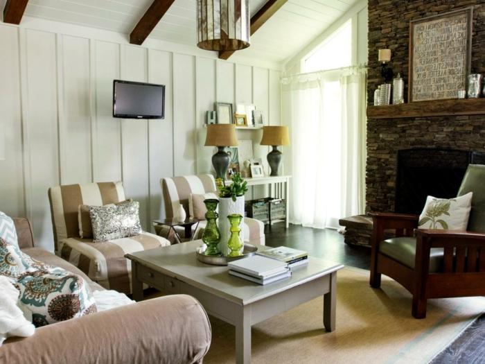 deco campagne chic rustique, table basse en bois gris, canapé marron clair et fauteuil à rayures marron et blanc, tapis fauve, chaise en bois vintage, cheminée en pierre, mur couleur blanche, poutre apparente