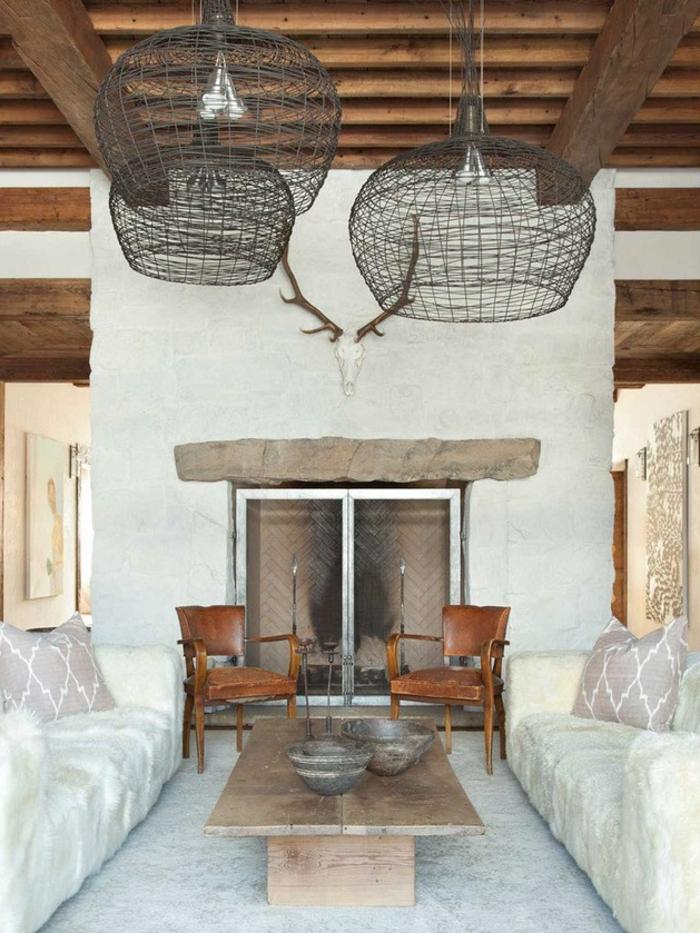 salon rustique, tapis gris clair, canapé, couverture de fourrure blanche, table basse en bois brut, chaises en bois, suspensions en métal, maison ossature bois