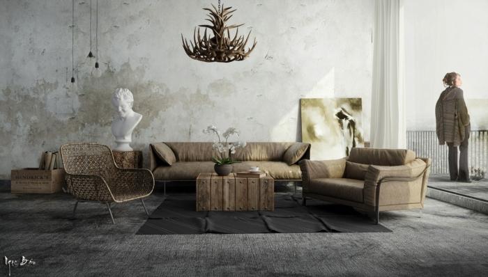 deco contemporaine, salon industriel rustique, susoension décorative de bois de cerf, tapis gris, canapé et fauteuil gris marron, table basse en palette de bois brut, mur défraîchi