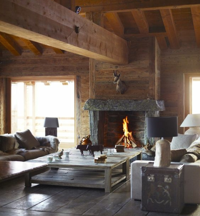 cheminée en pierre, maison ossature bois, table basse en bois gris, grands canapés gris, parquet en bois façon rustique, deco murale trophée de chasse, salon rustique