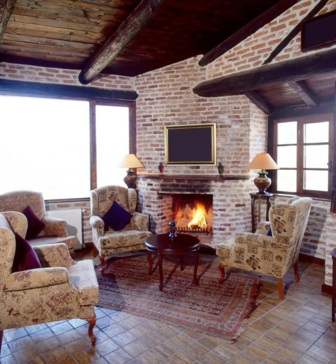mur en briques, sol en pierre, fauteuils vintage, petit tapis oriental, table basse en bois, maison ossature bois, salon rustique