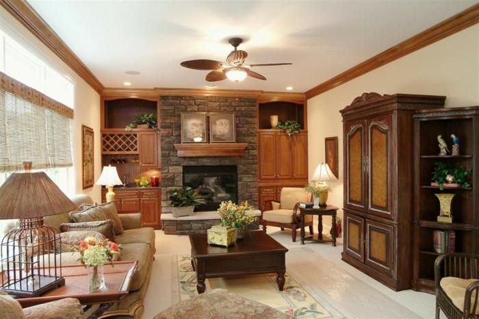 deco campagne chic rustique salon, canapé gris, table basse en bois marron, tapis à motifs floraux, armoire en verre, cheminée en pierre,