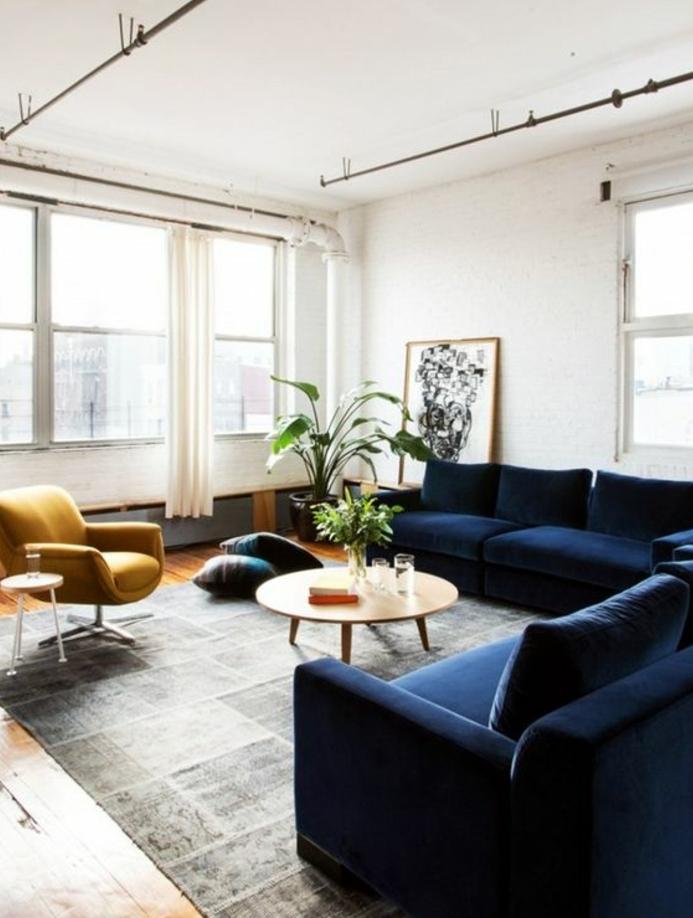 exemple salon scandinave blanc, tapis gris, canapé bleu marine et fauteuil jaune moutarde, table basse en bois, parquet clair, deco dessin noir et blanc abstrait
