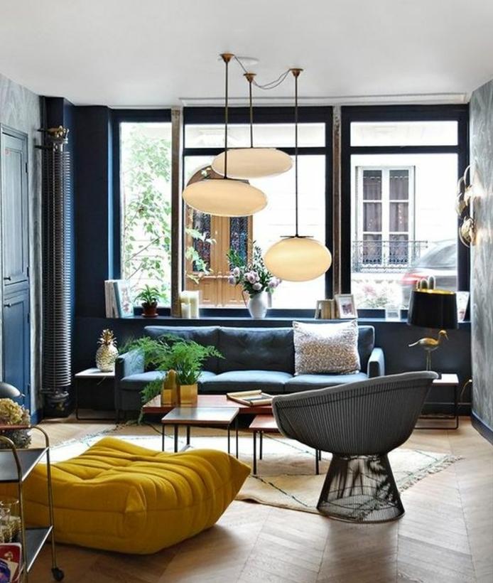 amenager un salon scandinave, canapé mur couleur bleu marine, parquet clair, pouf jaune, table basse en bois, fauteuil moderne