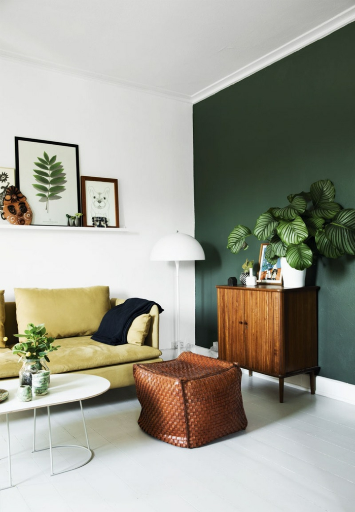salon dans l'esprit de la tendance nature, mur d'accent vert et canapé ocre jaune tirant ver le beige