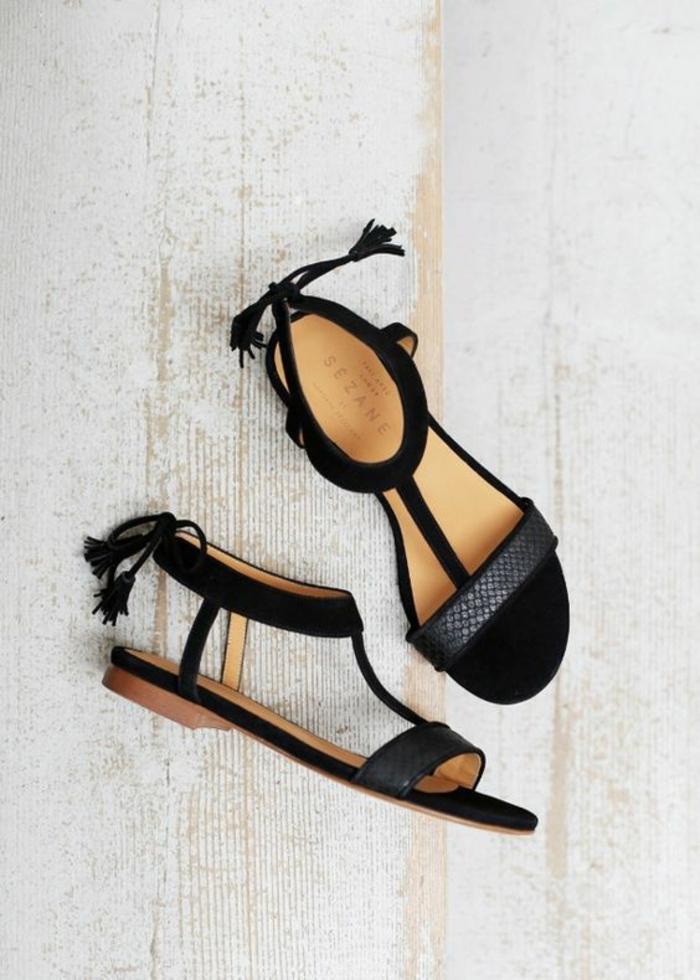 sandale femme noire plate avec des pompons derrière et une lanière aux motifs serpent devant